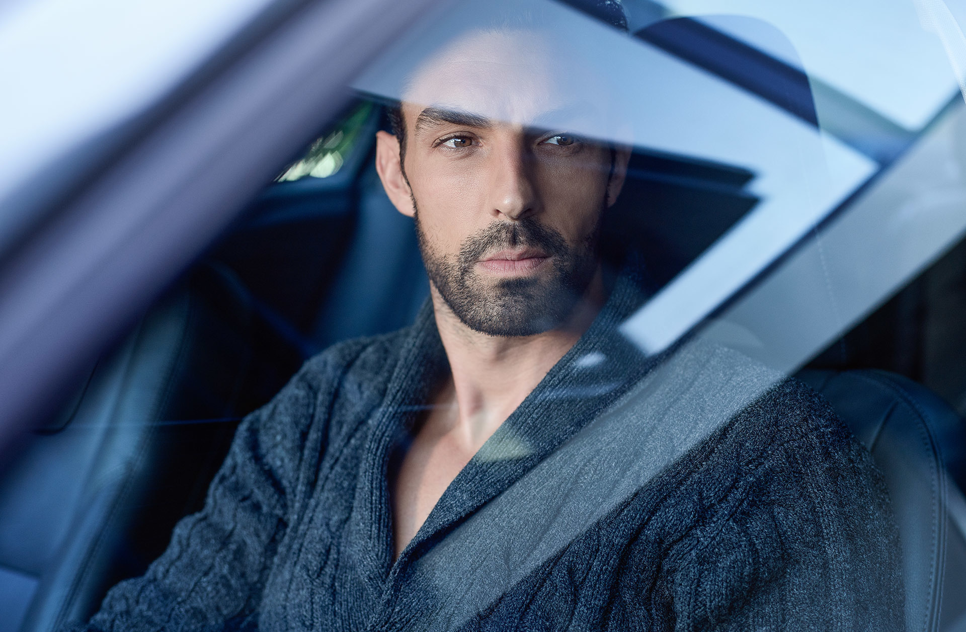 Man in front seat of car thoughtfully looking along
