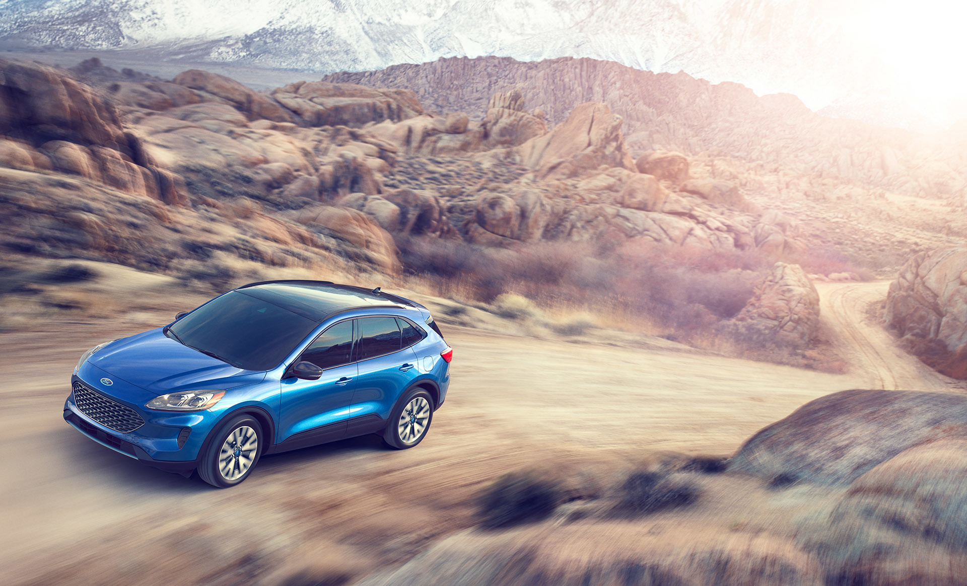 Blue CUV automobile driving up between hills